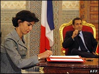 The Justice Minister, Rachida Dati, signs a deal in the presence of Mr Sarkozy