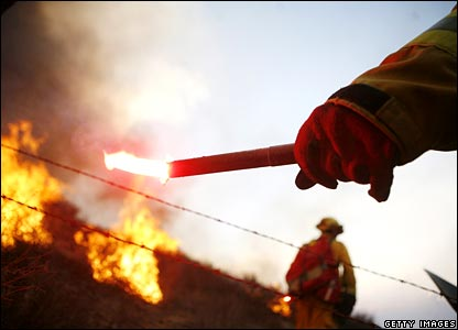 Firefighters light backfires to try to protect the Bonita neighbourhood of San Diego, on Tuesday