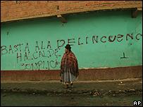 """Una mujer boliviana frente a un muro que reza: """"Basta a la delincuencia, alcalde cómplice"""""""