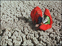 Two Indian women sitting on parched soil (Image: AP)