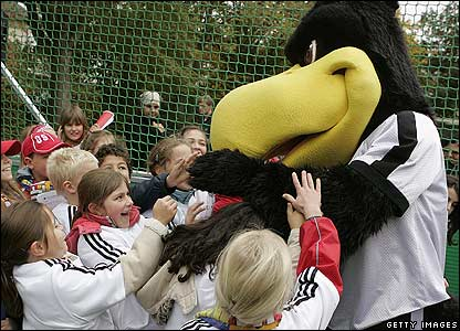 A mascot playing with children at football field in Germany