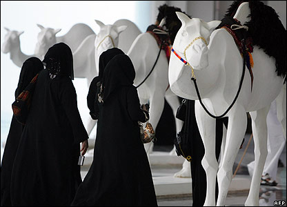 Women admiring camel models at an exhibition in Abu Dhabi