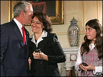 President Bush kisses Yamile Llanes Labrada (C) as Melissa Gonzalez (R) looks on, both refugees from Cuba