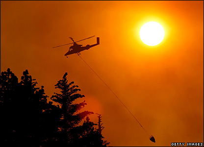 A helicopter carries an empty bucket in Running Springs, California, 24 October 2007