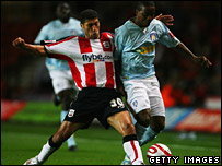 Southampton's Youssef Safri tackles Kevin Lisbie of Colchester United
