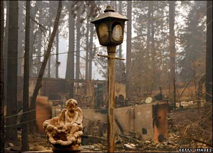 A statue and lamp post stand at the site of a burned home in Running Springs, 24 October 2007