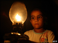 A Palestinian girl holding a lamp during a blackout in Gaza (17 August 2007)