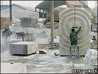 Un obrero chino trabaja una escultura que se utilizará en las Olimpíadas