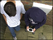 Boys playing with handheld game console, BBC