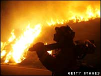A firefighter with a chainsaw at a blaze on the La Jolla Indian Reservation, California, in the early morning of 25 October 2007