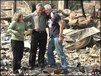 Mr Bush with Jay and Kendra Jeffcoat in the rubble of their San Diego home