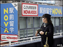 A woman walks past a Nova language school in Tokyo on 26 October 2007