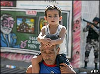 A man carries his son on his shoulders as he crosses a street of the Grotao favela -part of the Alemao shantytown complex, Rio de Janeiro, Brazil, 13 June 2007