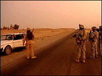 US soldiers stand by a car they have stopped on the roadside