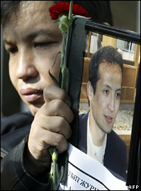 A person holds a portrait of murdered journalist Alisher Saipov outside the Kyrgyz interior ministry in Bishkek (26 October 2007)