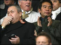 Carson Yeung and David Sullivan clap from the stands