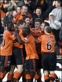 United team-mates congratulate scorer Lee Wilkie (centre)