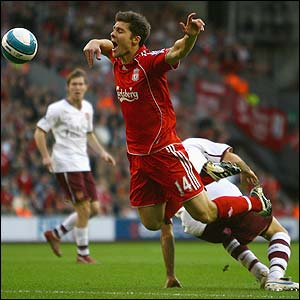 Liverpool's Xabi Alonso is felled by Cesc Fabregas