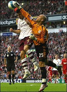 Liverpool's keeper Jose Reina punches the ball clear
