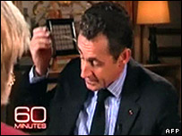 French President Nicolas Sarkozy takes off his microphone during the CBS interview.