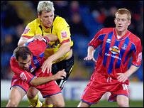 Watford's Darius Henderson challenges Carl Fletcher for the ball as Ben Watson looks on