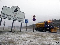 A road gritter passes a Highland region sign on the A9