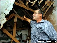 Israeli man shows damage to house in Sderot from Qassam rocket