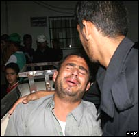 Palestinian men cry following an Israeli strike on Khan Younis, southern Gaza Strip, 30 October 2007