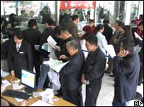Customers queue up for the first round of Olympic ticket sales at a branch of Bank of China in Fuyang