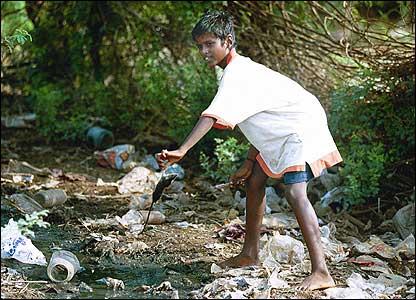 Boy with a rat in communal washing area of Tamil Nadu