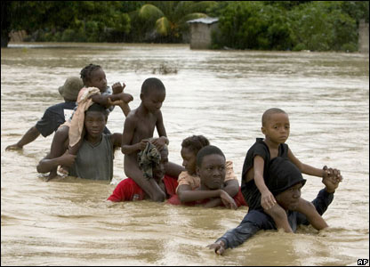 People struggle to cross a flooded street in La Plaine, Port-au-Prince, Haiti, 30 Oct