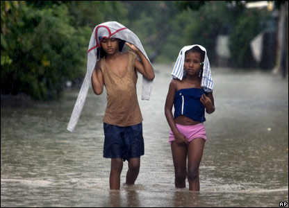 Two girls walk through an area flooded by heavy rains in San Cristobal, west of Santo Domingo, Dominican Republic, 30 Oct
