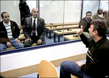 Suspect Mahmoud Slimane Aoun (r) signals to Youssef Belhadj (l) and Mouhannad Almallah Dabas inside a glass cage in the Madrid court