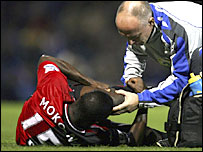 Aaron Mokoena receives treatment before being stretchered off at Fratton Park