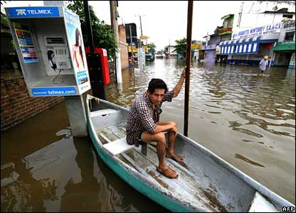 A man waits in a boat in the flooded streets of Villahermosa