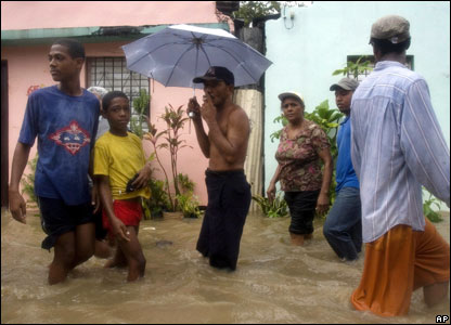People walk in a flooded street in Santo Domingo, 31 October