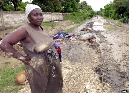 A woman stands in a flooded road in Cite Soleil, Port-au-Prince, Haiti, 1 November