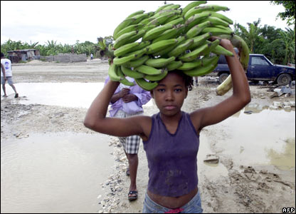 A Haitian girl carries bananas on her head in a flooded street in Cite Soleil, 1 November