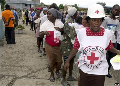 A member of the Red Cross helps pregnant women standing in line in Cite Soleil, 1 November