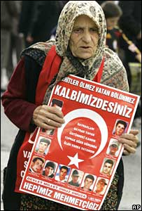 Turkish woman holds poster with pictures of dead Turkish soldiers