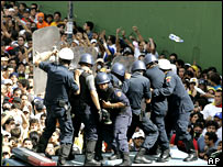 Riot police officers protect themselves as university students protest in Caracas, Thursday, Nov. 1, 2007