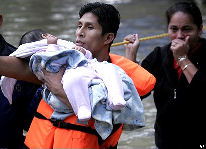 Rescuer carrying baby, watched by mother