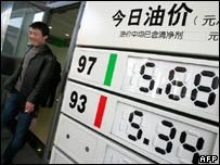 A man walks past a board showing fuel prices