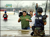 People wade across a flooded avenue in Villahermosa as a soldier keeps guard