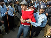 Pakistani policemen arrest a civil rights activist who was trying to march towards ousted chief justice Iftikhar Muhammad Chaudhry's house