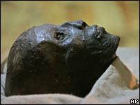 The face of the linen-wrapped mummy of King Tutankhamun is seen in a glass case in his underground tomb in the Valley of the Kings