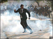 A Pakistani lawyer throws a rock at police amid tear gas fumes