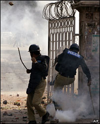 A police officer kicks a tear gas canister towards lawyers protesting against President Musharraf in Lahore on 5 November 2007
