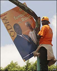 Kenyan hoisted up a pole holds a poster of the Orange Democratic Party candidate, Raila Odinga