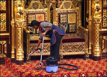 A cleaner vacuums the thrones prior to the State Opening of Parliament in London